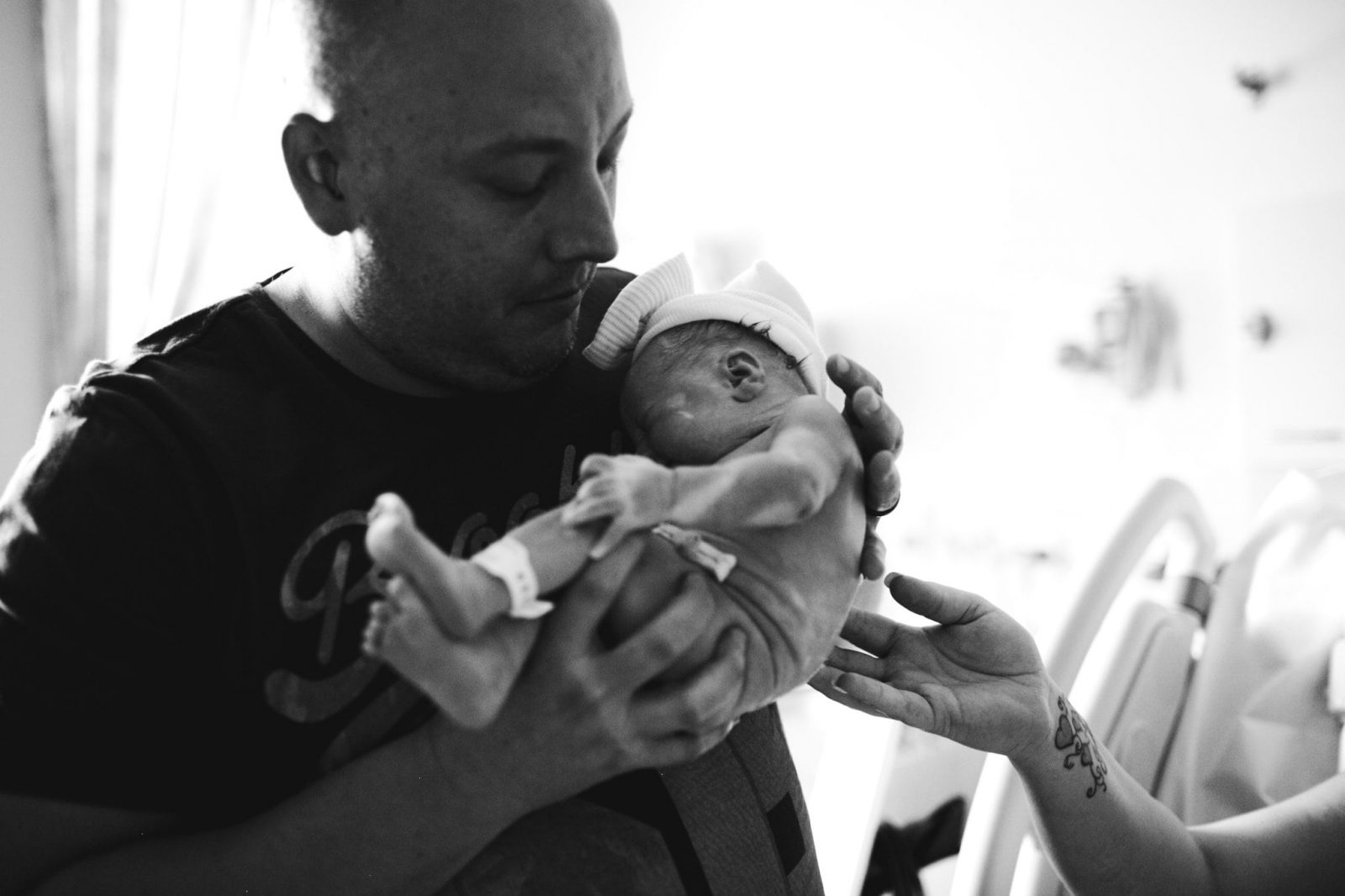 photograph of father holding newborn baby girl for the first time at wollongong hospital maternity ward