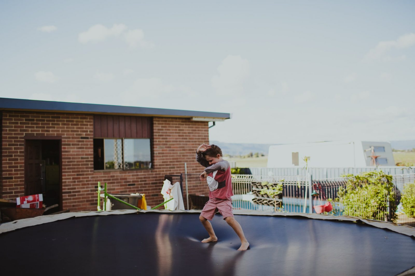 Photograph of kids playing on the trampoline in the back garden at home in Nowra during home documentary session on the South Coast of NSW