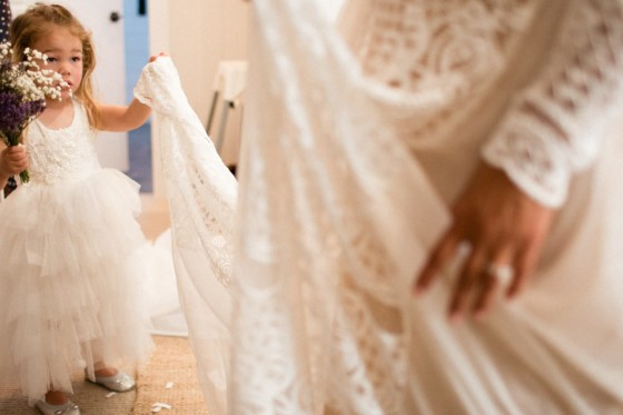 brides daughter holds mothers wedding dress chain