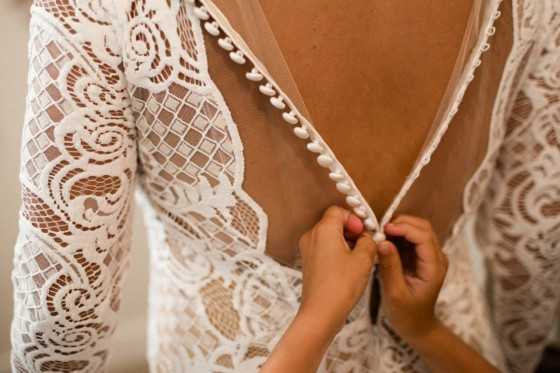 bride and grooms daughter helps mother put on wedding going