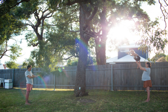 photograph of mum and dad pushing on the swings at home in wollongong