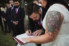 photograph of beautiful tattooed bride and her husband signing the registry