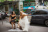 photograph of bride doing up her shoe on the way to wedding reception